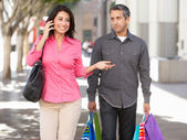Fed Up Man Carrying Partners Shopping Bags On City Street — Stockfoto