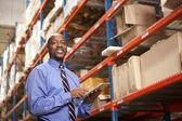 Empresario con portapapeles en almacén — Foto de Stock