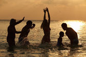 Silhouette Of Multi Generation Family Having Fun In Sea — Stock Photo
