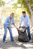 Couple Picking Up Litter In Suburban Street — 图库照片