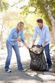 Couple de ramasser les déchets dans la rue de banlieue — Photo