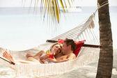 ρομαντικό ζευγάρι χαλαρώνοντας στην αιώρα παραλία — Φωτογραφία Αρχείου