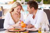 Pár těší jídlo v zahradní restauraci — Stock fotografie