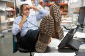 Zakenman voeten zetten op bureau in magazijn — Stockfoto