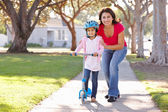 Mother Teaching Daughter To Ride Scooter — Stockfoto
