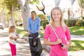 Mère et filles ramasser les déchets dans la rue de banlieue — Photo