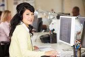 Woman With Headset Working At Desk In Busy Creative Office — Stock Photo