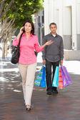 Dost muže který má partnery nákupní tašky na ulici města — Stock fotografie