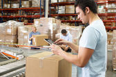 Werknemer met behulp van tablet pc in distributie magazijn — Stockfoto