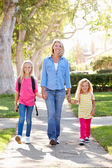 Mother And Daughters Walking To School On Suburban Street — Stock Photo