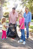 Familia recogiendo basura en la calle suburbana — Foto de Stock