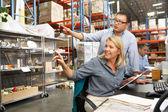Compañeros de trabajo trabajando en recepción en almacén — Foto de Stock