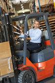 Homem dirigindo empilhadeira de garfo em armazém — Foto Stock