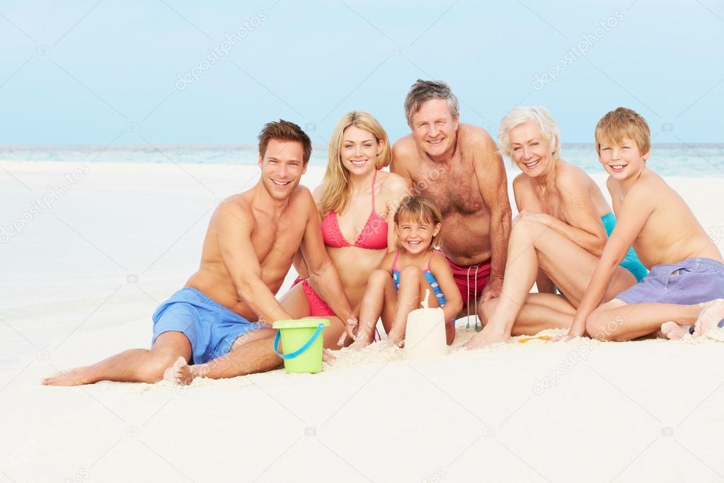 multi generation family having fun on beach holiday stock photo