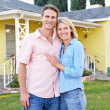 Stock Photo: Couple Standing Outside SuburbHome