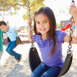 Boy And Girl Playing On Swing In Park - ストック写真