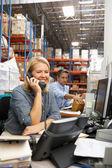 Zakenvrouw werken bij bureau in magazijn — Stockfoto