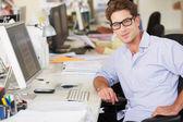 Homem trabalhando no balcão no escritório ocupado de criativo — Foto Stock