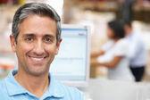 Man bij computer terminal in distributie magazijn — Stockfoto