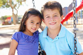 Boy And Girl Playing On Swing In Park — Stock Photo