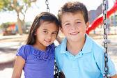 Niño y niña jugando en columpio en el parque — Foto de Stock