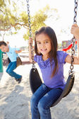 Boy And Girl Playing On Swing In Park — Stockfoto
