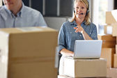 Female Manager Using Headset In Distribution Warehouse — Stock Photo