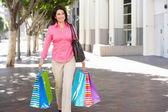 Donna che porta le borse della spesa sulla strada della città — Foto Stock