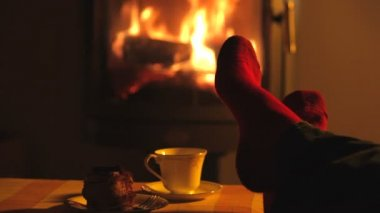 Man relaxes by warm fire and wriggles his toes. — Stock Video
