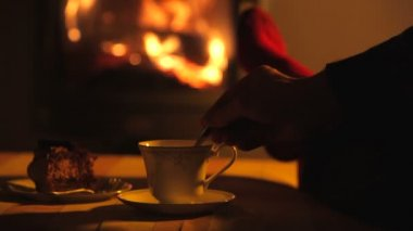 Man relaxes by warm fire then stirs drink with teaspoon — Stock Video