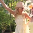 Two women wearing sunglasses and straw hats dance along country path. — Vídeo de stock