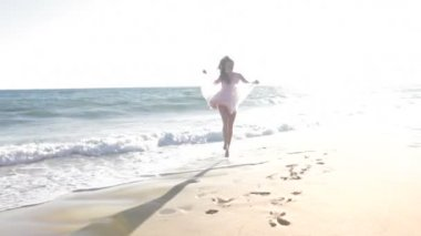Teenage girl dances along shoreline and kiss into camera. — Stock Video