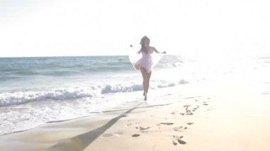 Teenage girl dances along shoreline and kiss into camera. — Stock Video