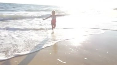 Little girl runs through surf — Stock Video