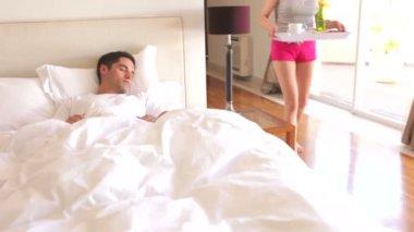 Kvinna förlägger bricka med frukost framför man i sängen. — Stockvideo