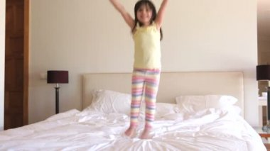 Young girl bounces excitedly on bed — Stock Video
