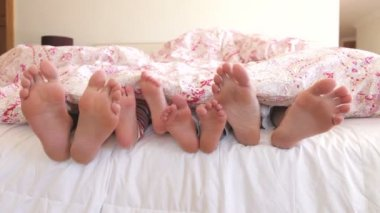Close up of feet wriggling as family wake up in bed. — Stock Video