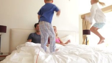 Boy and girl jumping on parents bed. — Stock Video