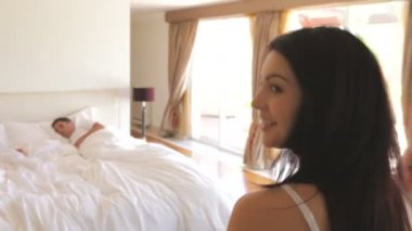 Kvinna hoppa på säng att väcka mannen — Stockvideo