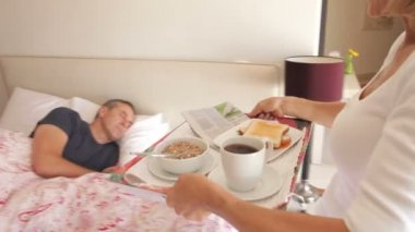 Woman places tray with breakfast in front of man in bed. — Stock Video