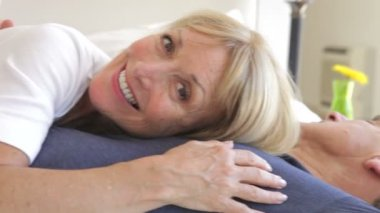 Senior woman lying on husbands chest — Stock Video