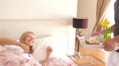 Man places tray with breakfast in front of woman in bed. — Stock Video