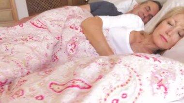 Sleeping senior couple as woman stretches — Stock Video