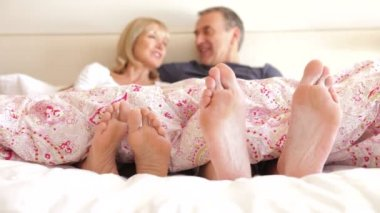 Close up of feet wriggling as senior couple sit up and chat in bed. — Stock Video