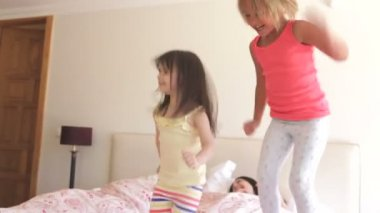 Daughters jumping on parents bed — Stock video