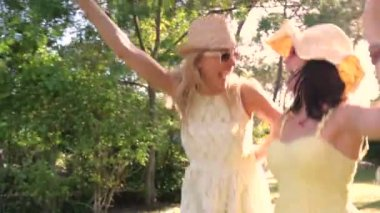 Two women wearing sunglasses and straw hats dance along country path. — Stock Video