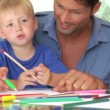 Father helping son as camera pans around to mother and daughter working on picture with pens together. — Stock Video #25302459