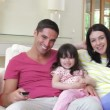 Stock Video: Family relaxing on sofa together watching tv as grandparents walk into frame and join them.