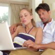 Happy couple relaxing on sofa with laptop — Stock Video