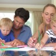 Father helping son and mother help daughter as they work on picture with pens — Stock Video